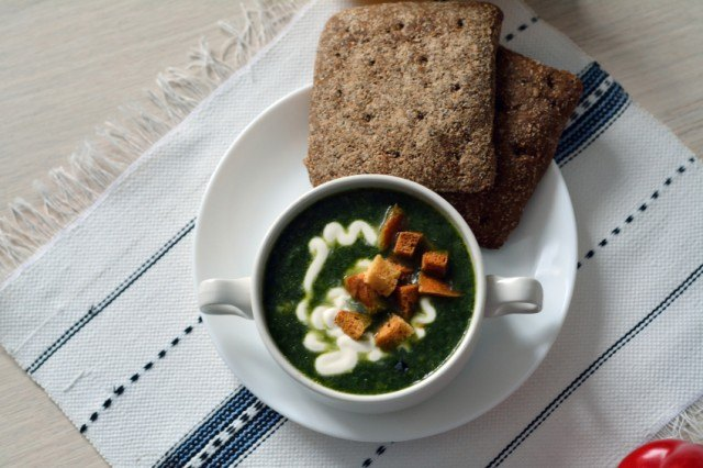 green soup with croutons and cream