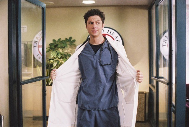 J.D. walking into Sacred Heart Hospital in scrubs and a white jacket, which he is holding open.
