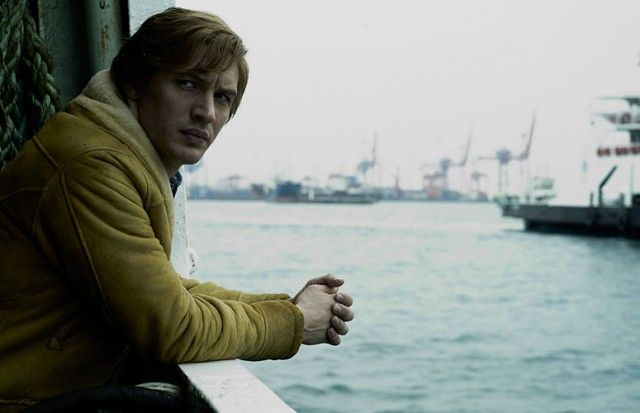 Tom Hardy leans on a railing while looking to on the water in Tinker Tailor Soldier Spy