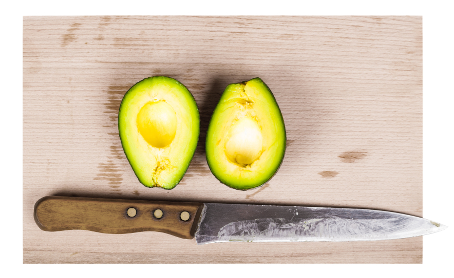 Avocado halved on a table with a knife