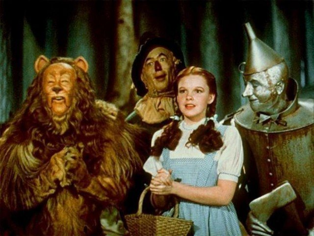 Dorothy, the Lion, Scarecrow, and Tin Man, gathered together, smiling in a forest