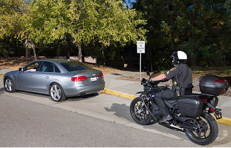 A cop on a motorcycle pulls over a car.