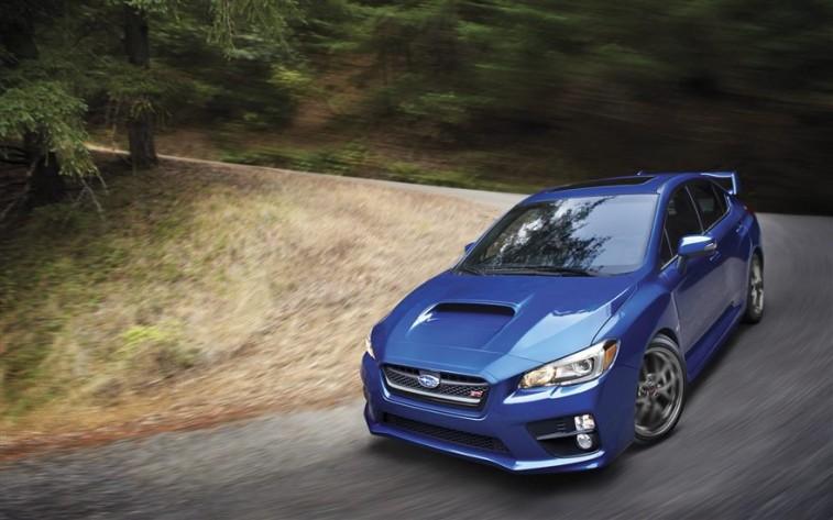 A blue 2015 Subaru WRX rounding a corner