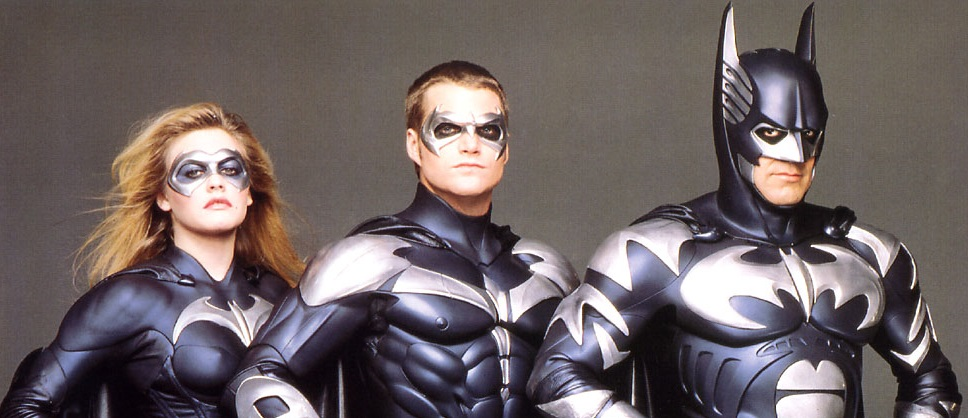 Batman and Robin stand in uniform looking into the camera in front of a grey background