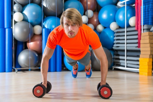 man using dumbbells to perform a plank exercise