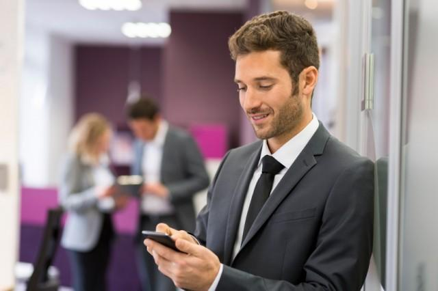 Businessman typing a message on mobile phone in modern office