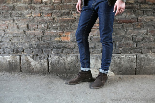 Man wearing blue jeans standing against wall
