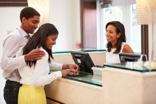 couple checking in at hotel front desk
