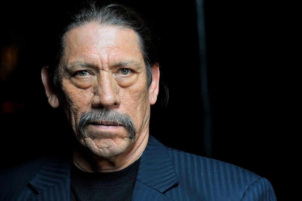Actor Danny Trejo in a blue suit jacket in front of a black backdrop