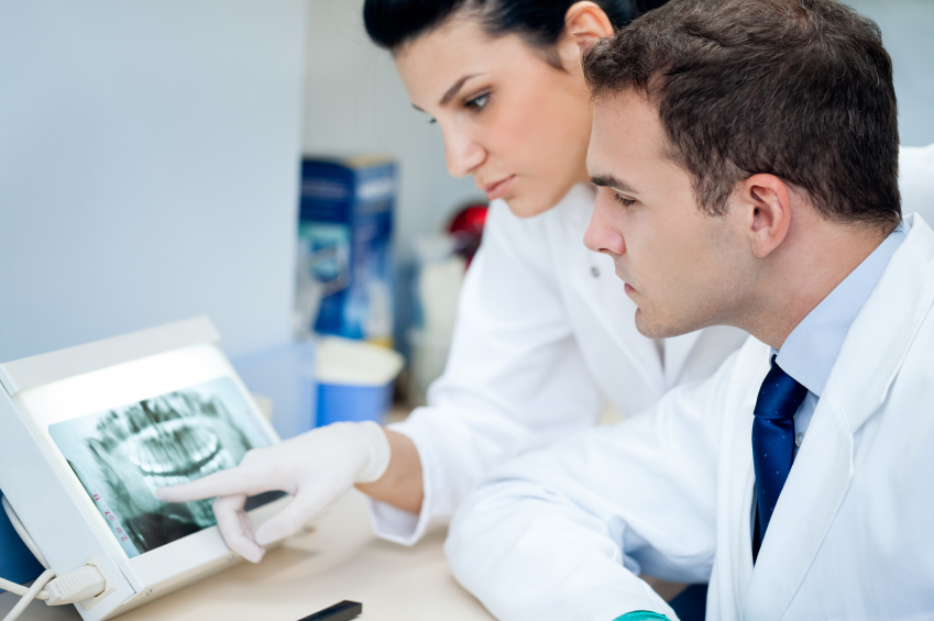 Dental professionals examine X-rays.