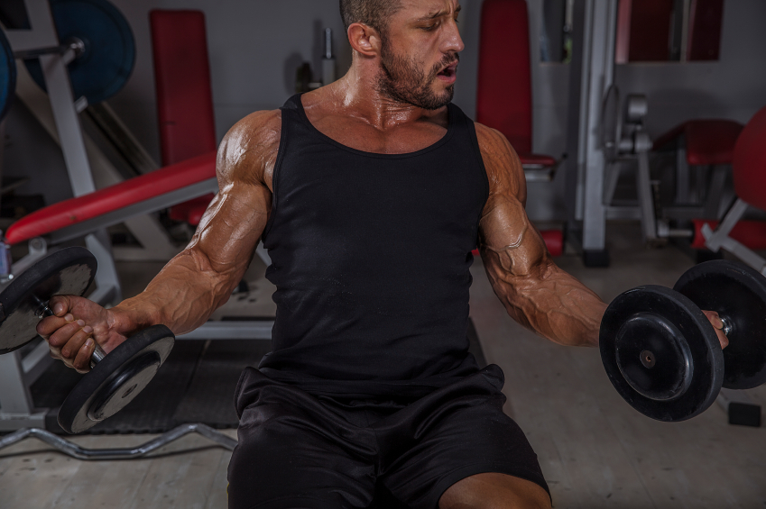 man performing dumbbell curls at the gym