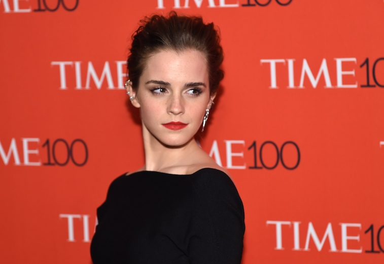 Emma Watson poses in a black dress on the red carpet.