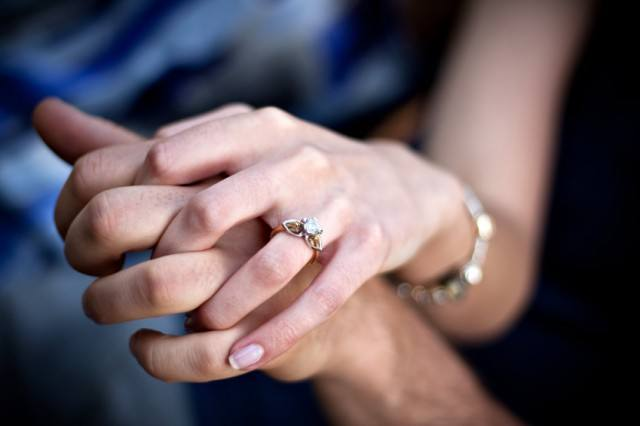 A woman holding her partners hand while wearing a diamond ring.