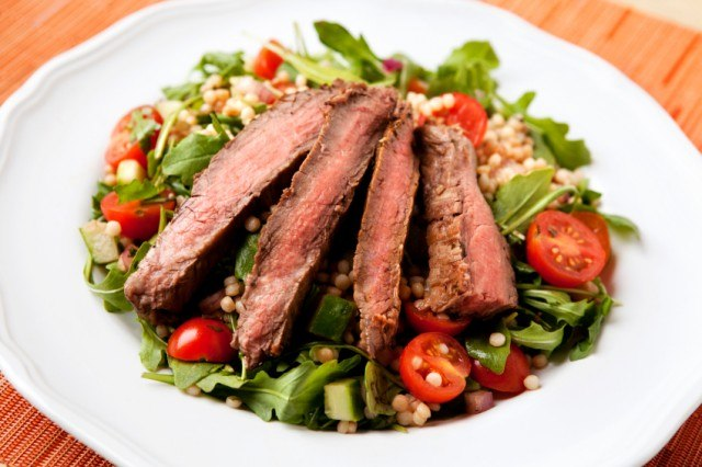 Salad topped with grilled steak for added flavor