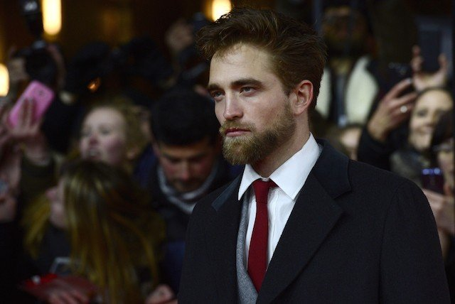 Robert Pattinson poses for cameras while fans group behind him