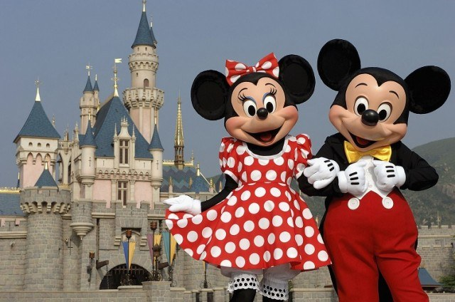Mickey and Minnie Mouse characters in front of castle