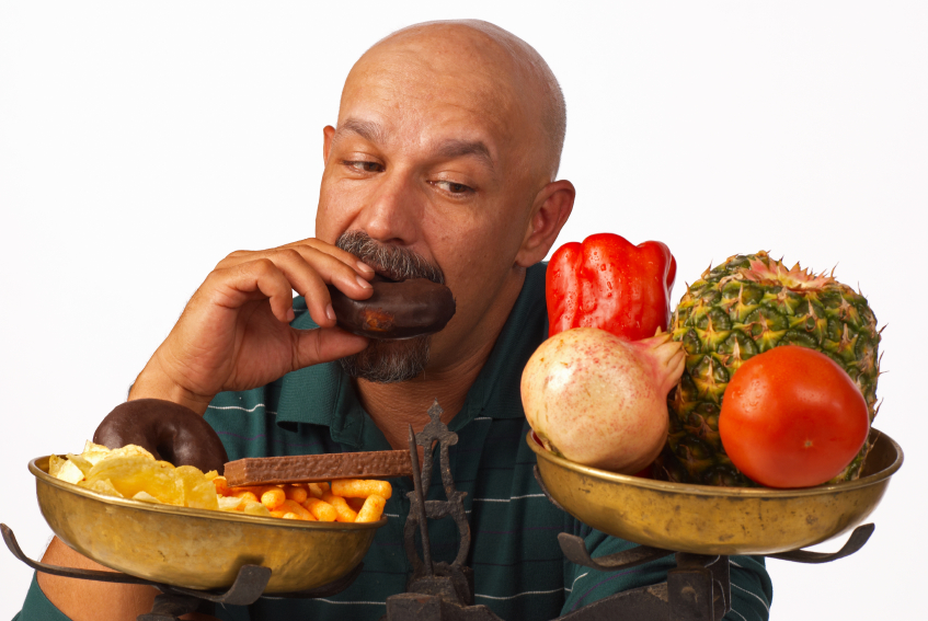 A man deciding between healthy food and junk food