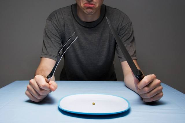 man looking hungrily at his empty plate