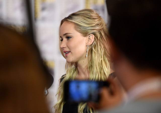 Jennifer Lawrence being photographed on a phone as she talks to someone in front of her.