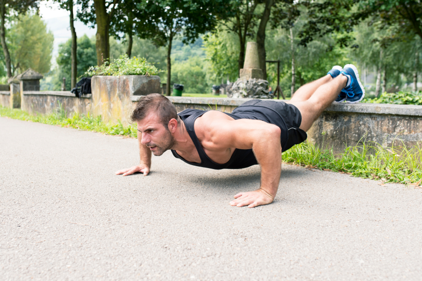 Man doing push-ups with feet elevated in the park