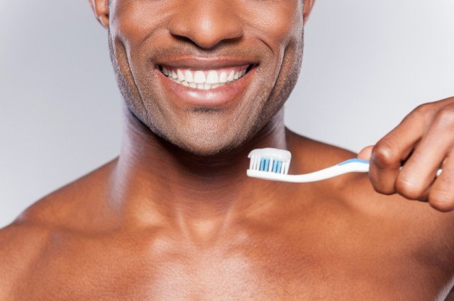 Man smiling while holding a toothbrush