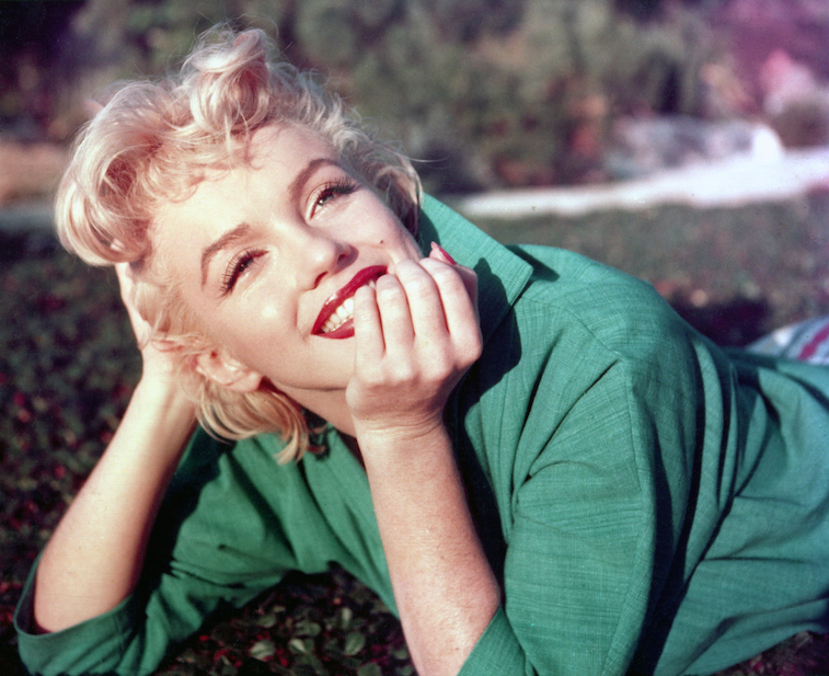 Marilyn Monroe smiling, poses in the grass for a portrait