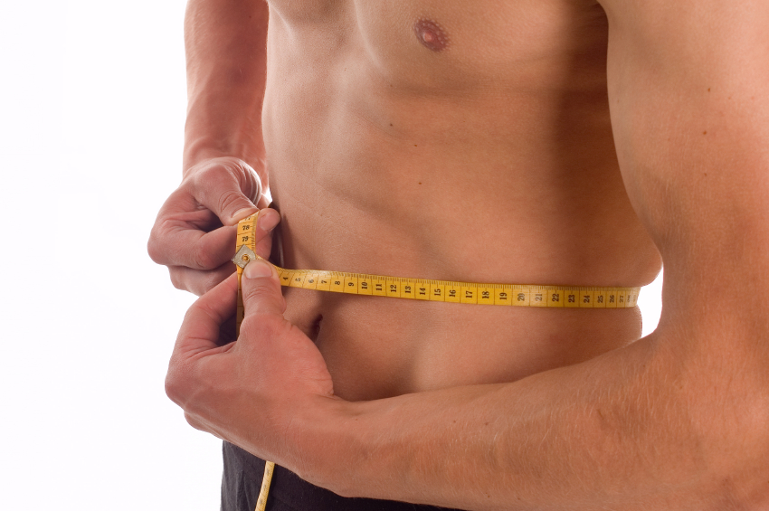 close-up of a man measuring his waist with a tape measure