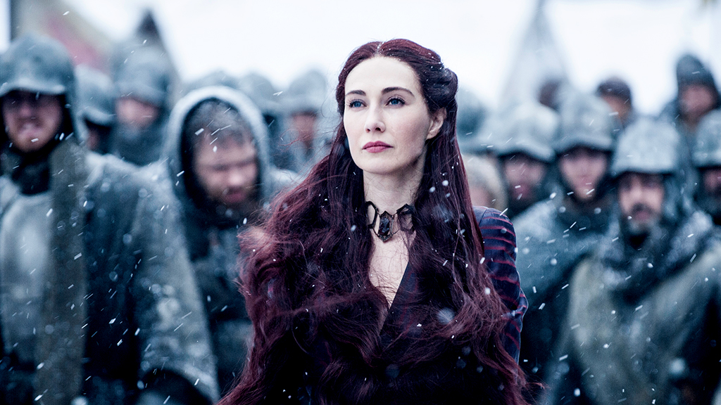 Melisandre stands among soldiers in the snow.