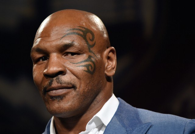 Mike Tyson in a suit looks at camera and shows off his face tattoo