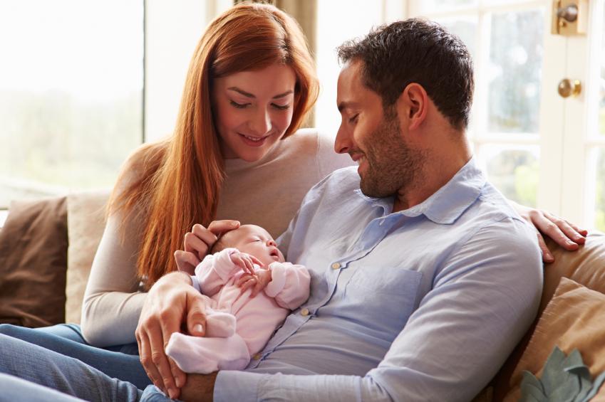 happy couple cradling their sleeping newborn
