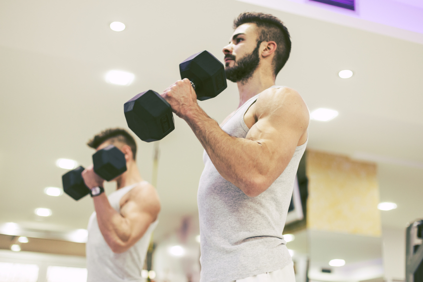 Muscular Bodybuilders Doing Exercises with Dumbbells in Gym