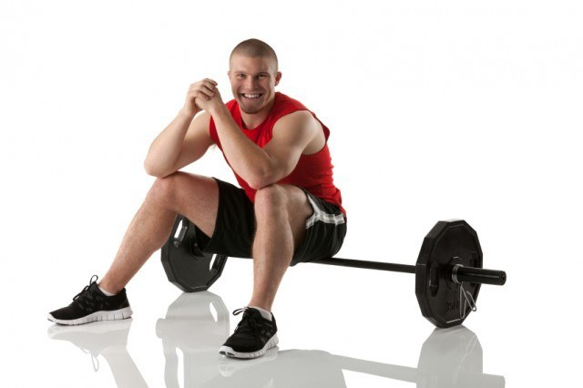 muscular man sitting on a barbell