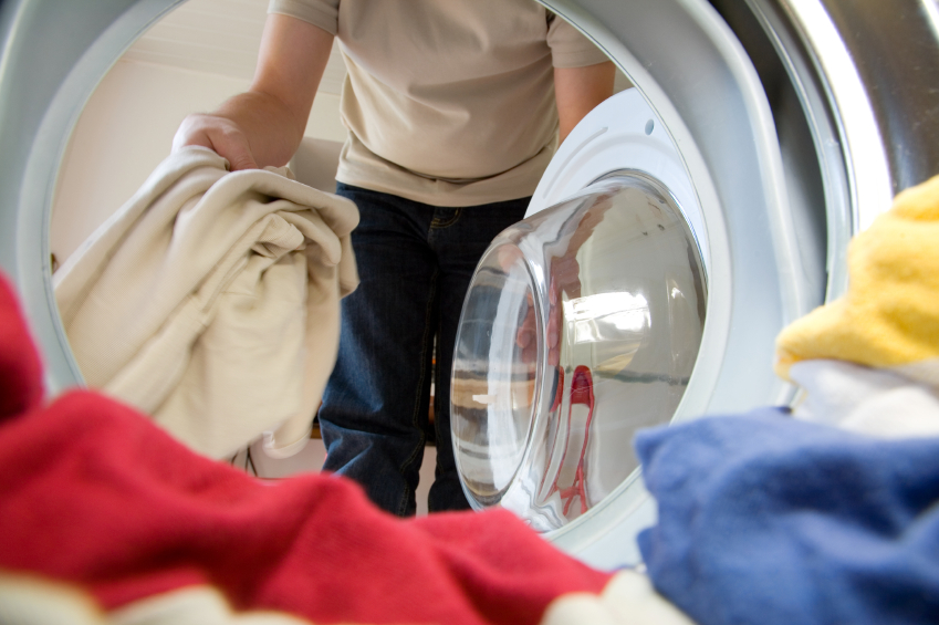 A man pulls clothes out of the dryer.