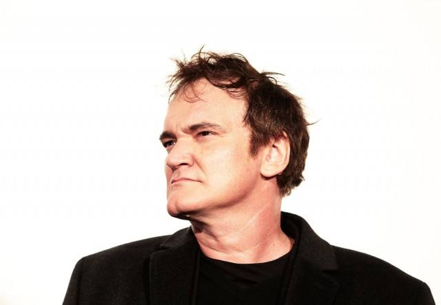 Quentin Tarantino wearing a black jacket and shirt in front of a white background.