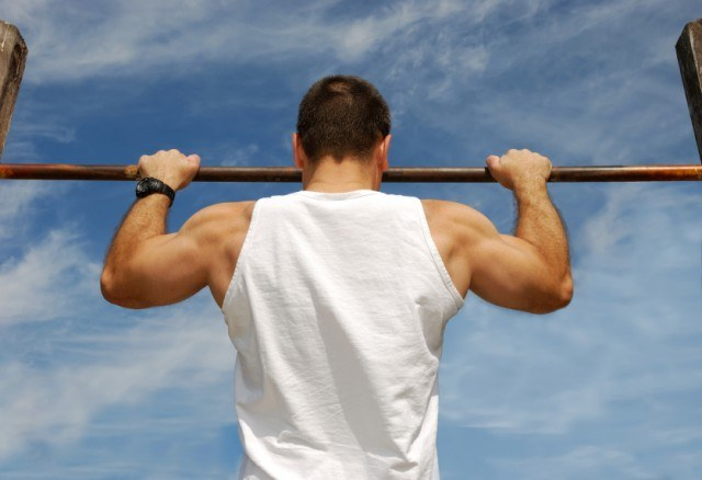 muscular man in a white tank doing pull-ups