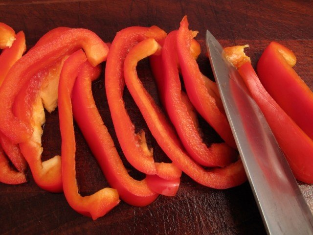 strips of red bell pepper being sliced