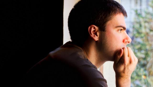 Sad man looking out of the window