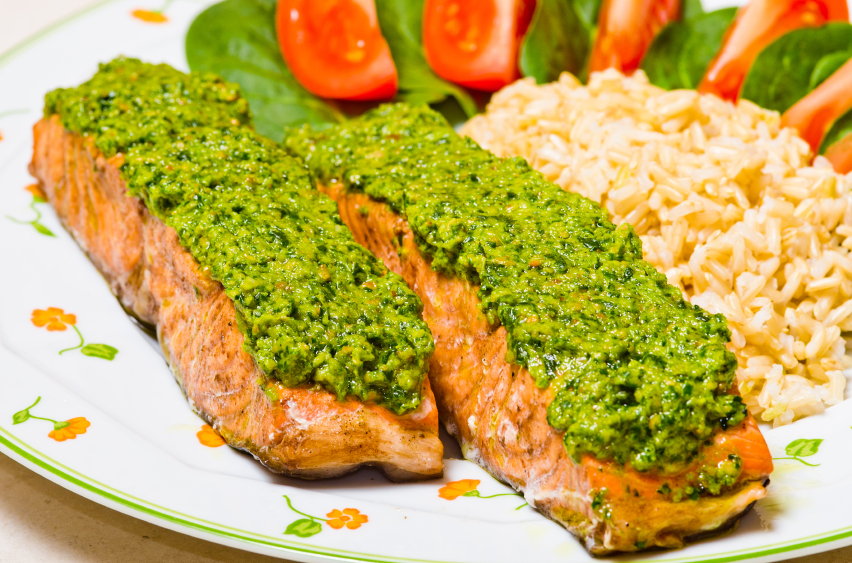 salmon topped with pesto served with rice and a salad