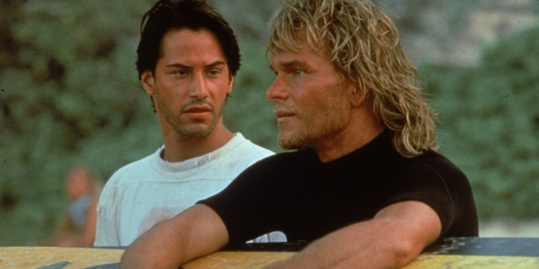 Keanu Reeves looks at Patrick Swayze as they sit on a beach in Point Break.