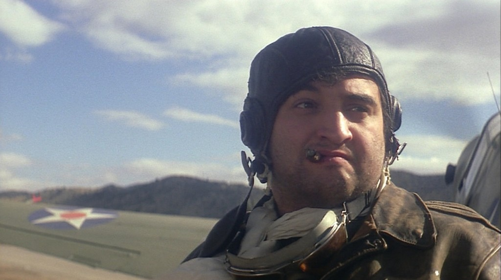 John Belushi is dressed as a pilot with a cigar in his mouth.