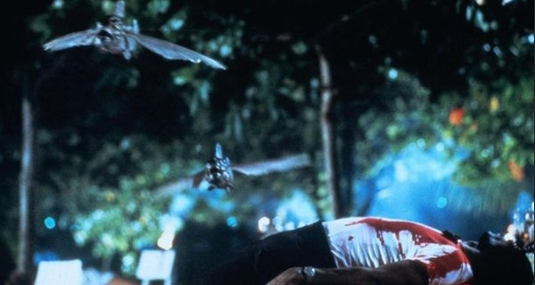 A dead bloody man lies on the ground as piranhas jump over him in Piranha II: The Spawning.