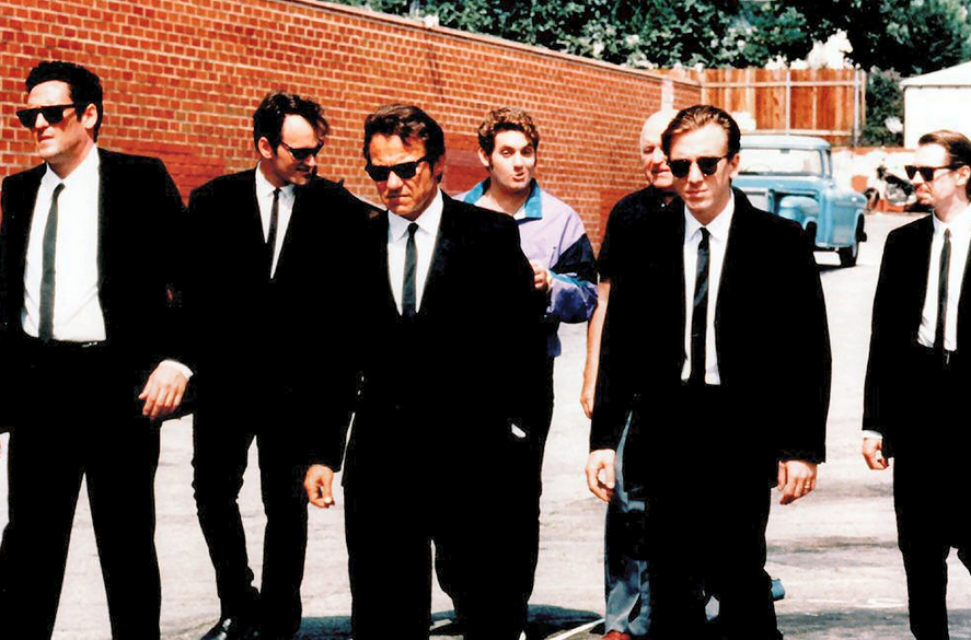 The cast of Reservoir Dogs are walking outside in black suits.