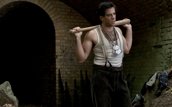 Eli Roth with a bat on his shoulders, wearing a white tank top