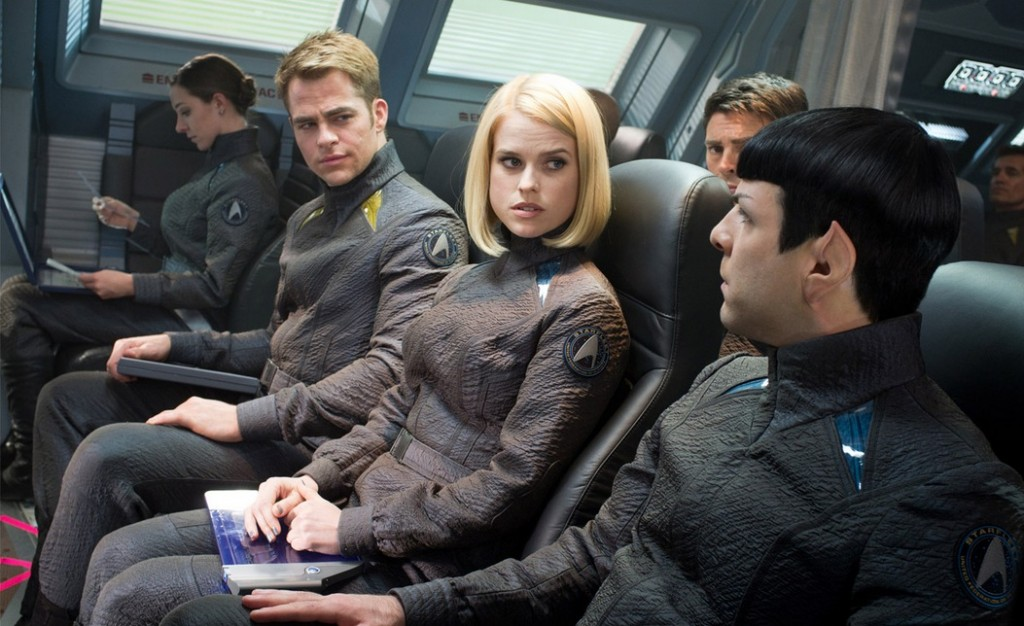 The cast of Star Trek Into Darkness are seated next to each other in a ship.