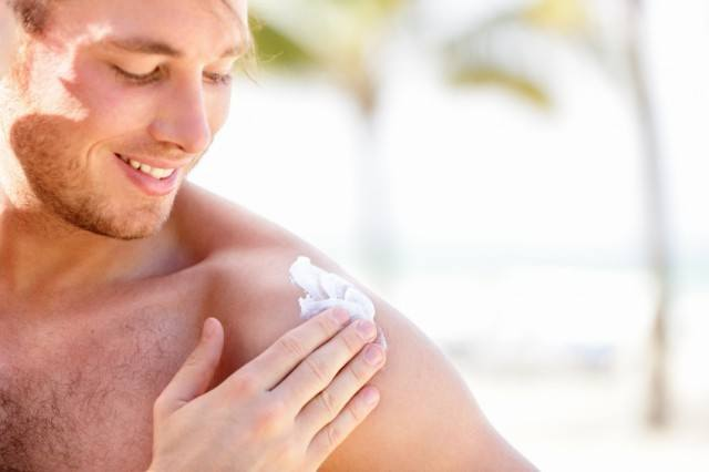 man rubbing sunscreen onto his shoulder