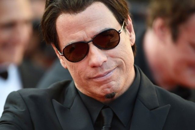 John Travolta wearing a black suit and dark sunglasses.