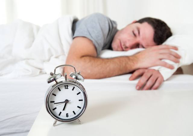 Man sleeping in bed before alarm sounds