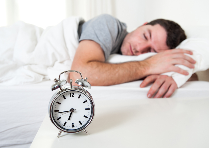 Man sleeping in his bed next to an alarm clock