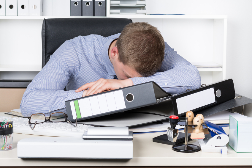 young man working in a n office slumped over desk