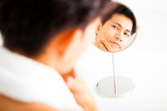 Man lightly touching his face while looking in the mirror